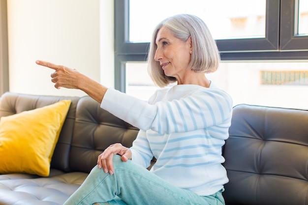 Mujer bonita de mediana edad de pie y apuntando al objeto en el espacio de la copia, vista trasera