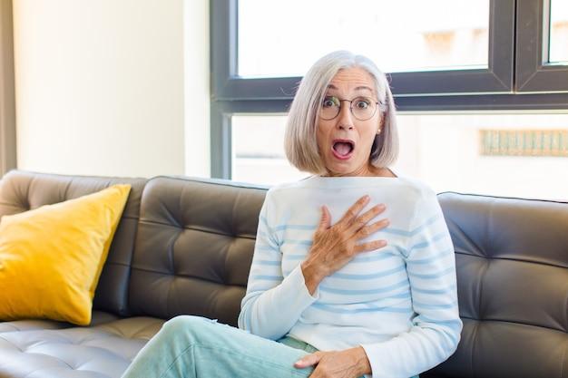 Mujer bonita de mediana edad que se siente conmocionada y sorprendida, sonriendo, tomando de la mano, feliz de ser la indicada o mostrando gratitud