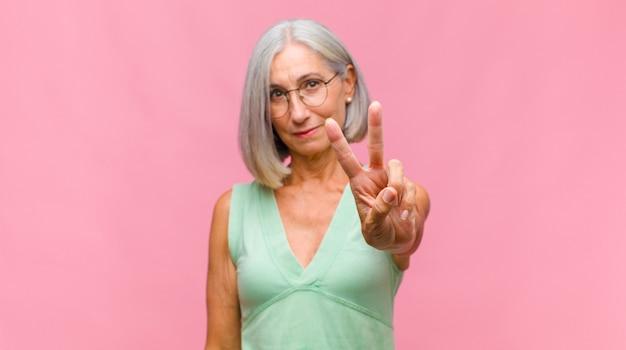 Mujer bonita de mediana edad que se siente feliz, asombrada, satisfecha y sorprendida, mostrando gestos de aprobación y pulgar hacia arriba, sonriendo