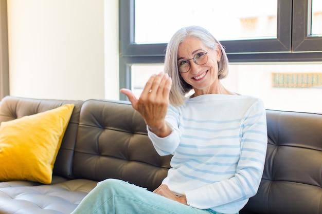 Mujer bonita de mediana edad que se siente feliz, exitosa y segura, enfrenta un desafío y dice: ¡adelante! o dándote la bienvenida