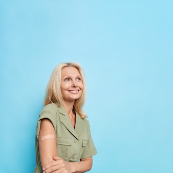 Mujer bonita de mediana edad rubia complacida pensativa usa vendaje adhesivo en el brazo feliz después de hacer la vacunación enfocada sobre poses contra la pared azul