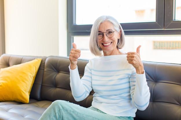 Mujer bonita de mediana edad sonriendo ampliamente con aspecto feliz, positivo, seguro y exitoso, con ambos pulgares hacia arriba