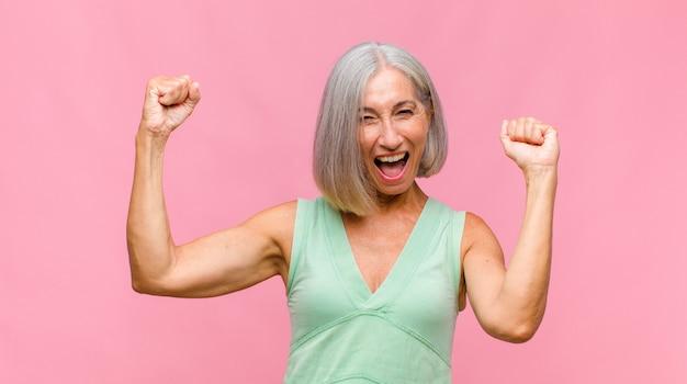 Mujer bonita de mediana edad sonriendo positivamente y con confianza con los brazos levantados