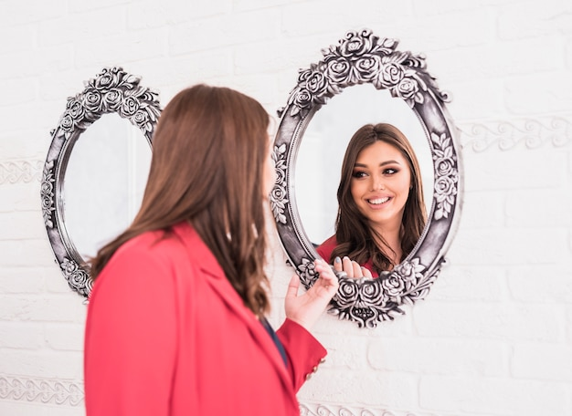 Mujer bonita mirando espejo