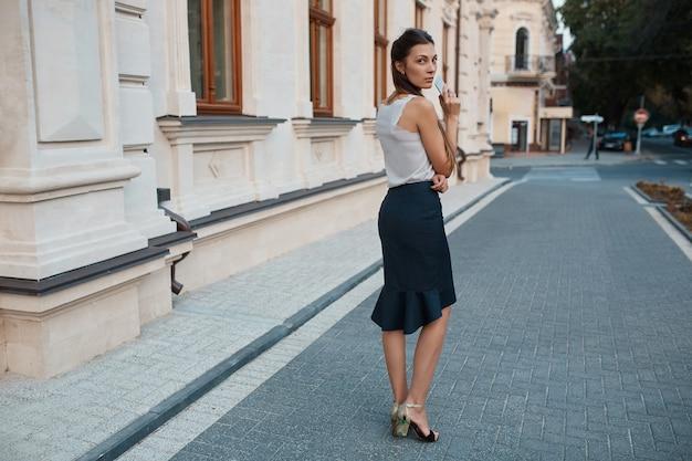 Mujer bonita de moda caminando por las calles de la ciudad vieja