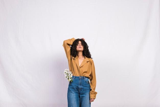 Mujer bonita negra con flores de margarita en el bolsillo de los pantalones vaqueros