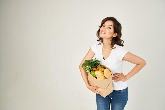 Mujer bonita en paquete de camiseta blanca con servicio de compras de comestibles