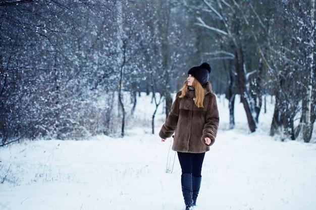 Mujer bonita en un parque de invierno