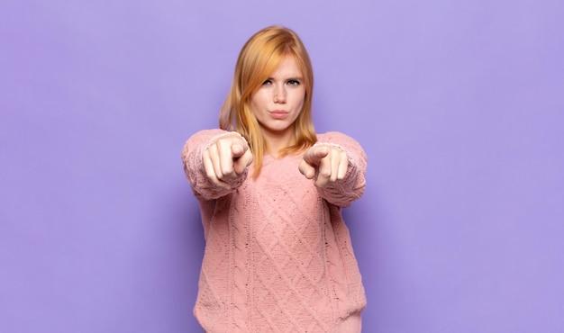 Mujer bonita pelirroja apuntando hacia la cámara con ambos dedos y expresión enojada, diciéndole que cumpla con su deber