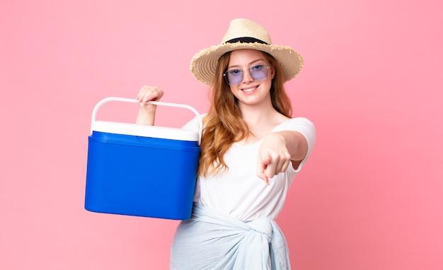 Mujer bonita pelirroja apuntando a la cámara eligiéndote y sosteniendo un refrigerador portátil de picnic