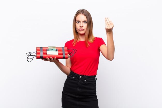 ¡mujer bonita pelirroja que hace gestos de dinero o capice, diciéndole que pague sus deudas! con una bomba de dinamita