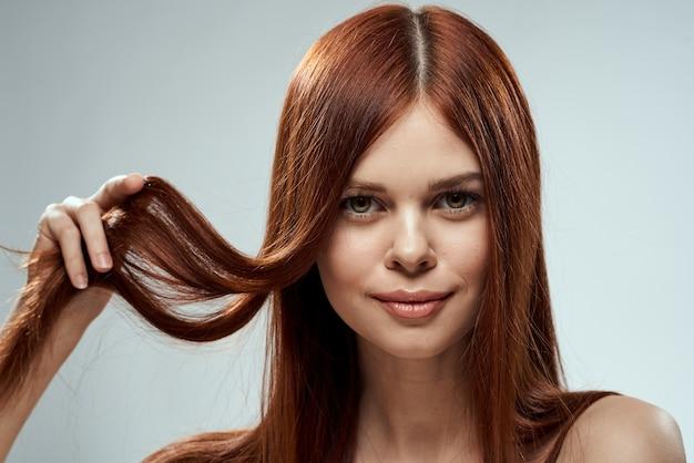Mujer bonita pelirroja sosteniendo su cabello con las manos arreglando el espacio de luz hombros desnudos.