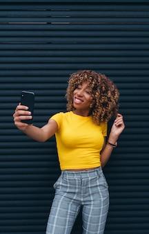 Mujer bonita con pelo afro mediante teléfono móvil.