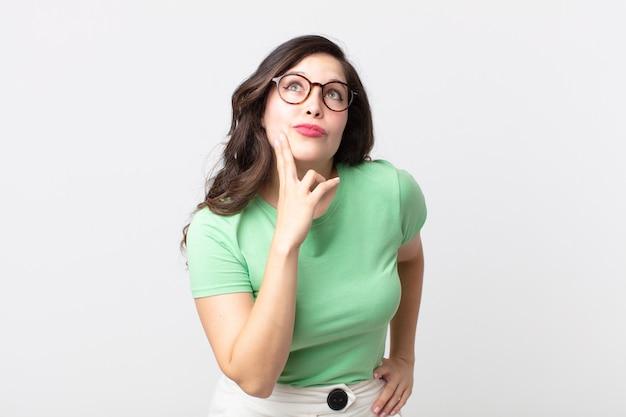 Mujer bonita pensando, sintiéndose dudosa y confundida, con diferentes opciones, preguntándose qué decisión tomar