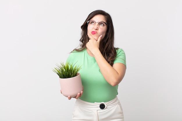 Mujer bonita pensando, sintiéndose dudoso y confundido y sosteniendo una planta decorativa