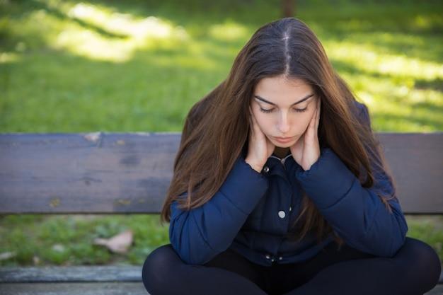 Mujer bonita pensativa que se sienta en banco en parque