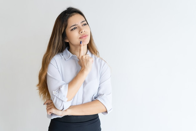 Mujer bonita pensativa tocando la barbilla con el dedo y mirando a otro lado