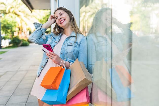Mujer bonita de pie con bolsas de la compra, teléfono inteligente y tarjeta de crédito