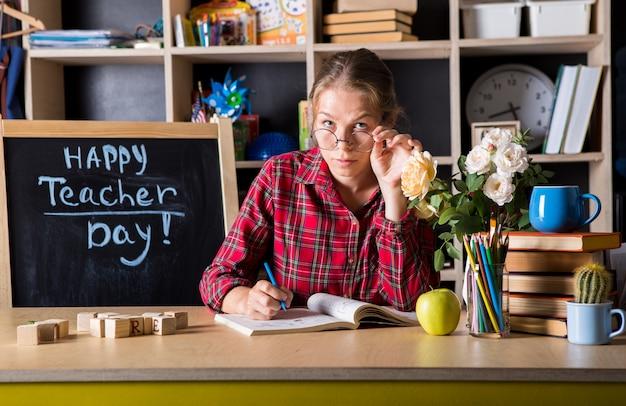 La mujer bonita del profesor disfruta del proceso educativo en sala de clase. día del maestro.