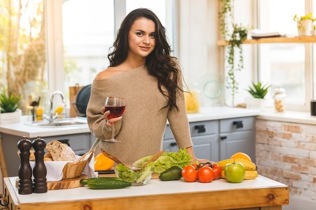 Mujer bonita que cocina y que bebe un poco de vino en casa en cocina.