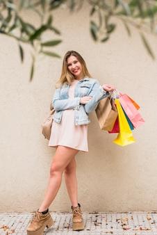 Mujer bonita que se coloca con los bolsos de compras brillantes afuera