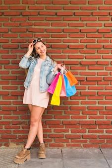 Mujer bonita que se coloca con los bolsos de compras brillantes en la pared de ladrillo