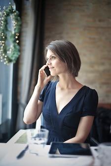 Mujer bonita que habla en un teléfono inteligente en un restaurante