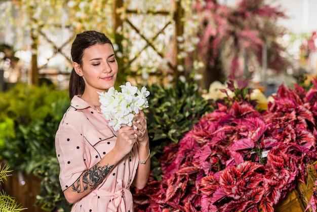Mujer bonita que huele flores blancas en casa verde
