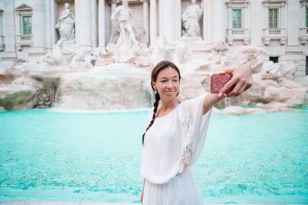 Mujer bonita que mira a la fuente de trevi durante su viaje en roma, italia. chica disfruta sus vacaciones europeas