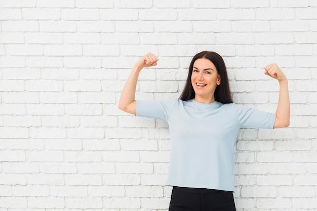Mujer bonita que muestra los músculos del brazo