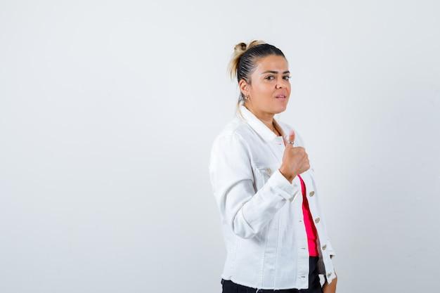 Mujer bonita que muestra el pulgar hacia arriba en la chaqueta blanca y parece confiada. vista frontal.