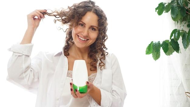 Mujer bonita que muestra el tubo cosmético blanco para el cuidado del cabello rizado en su mano en casa, sala blanca con plantas verdes