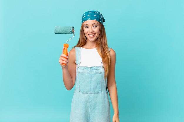 Mujer bonita que parece feliz y gratamente sorprendida pintando una nueva pared de casa