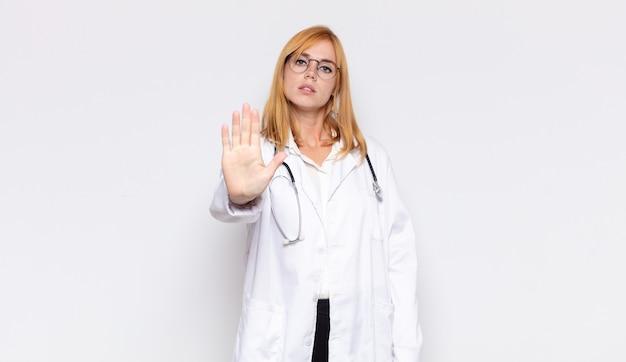 Mujer bonita que parece seria, severa, disgustada y enojada mostrando la palma abierta haciendo gesto de parada