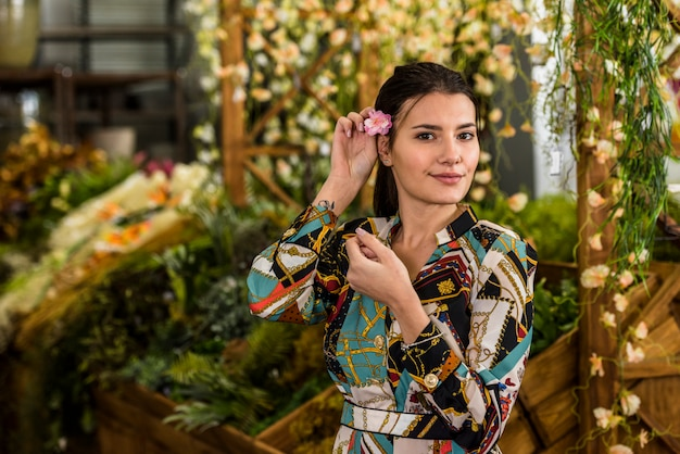 Mujer bonita que pone la flor en el pelo