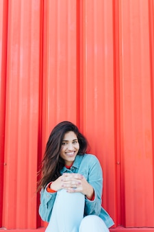 Mujer bonita que se sienta delante de fondo acanalado rojo