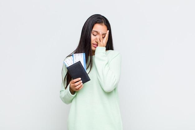 Mujer bonita que se siente aburrida, frustrada y con sueño después de una tarea tediosa, aburrida y tediosa, sosteniendo la cara con la mano