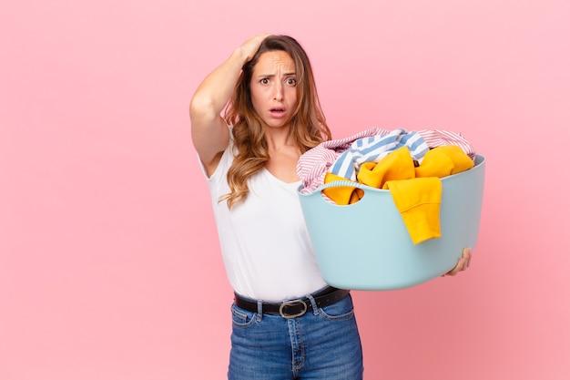 Mujer bonita que se siente estresada, ansiosa o asustada, con las manos en la cabeza y lavando la ropa.