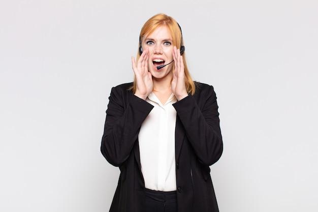 Mujer bonita que se siente feliz, emocionada y positiva, dando un gran grito con las manos al lado de la boca, gritando