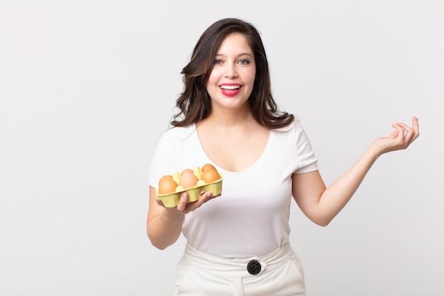 Mujer bonita que se siente feliz, sorprendida al darse cuenta de una solución o idea y sosteniendo una caja de huevos