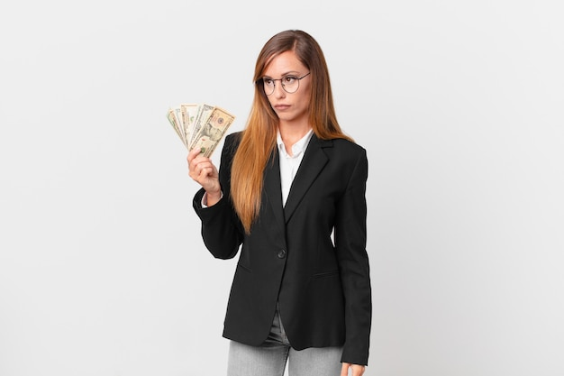 Mujer bonita que se siente triste, molesta o enojada y mira hacia un lado. concepto de negocio y dólares