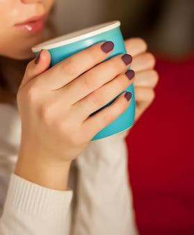 Mujer bonita que sostiene la taza azul de café o de té.