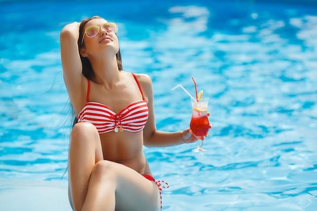 Mujer bonita que tiene un bronceado natural cerca de la piscina.