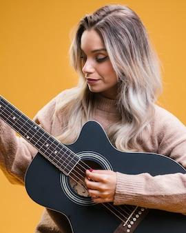 Mujer bonita que toca la guitarra contra fondo amarillo