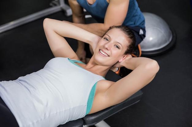 Mujer bonita que trabaja su abs en gimnasio