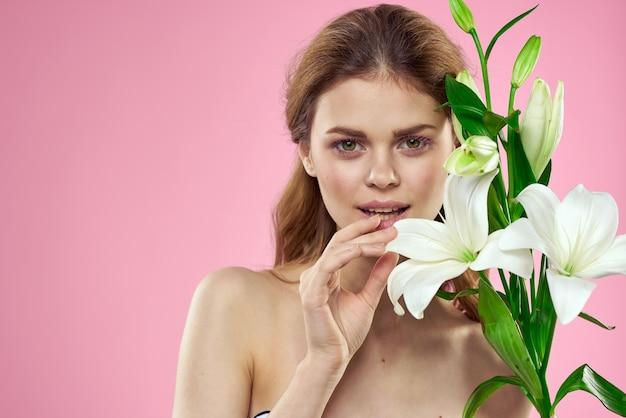 Mujer bonita con ramo de flores en las manos hombros desnudos encanto de fondo rosa. foto de alta calidad