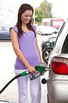 Mujer bonita reabastecimiento de combustible de su coche