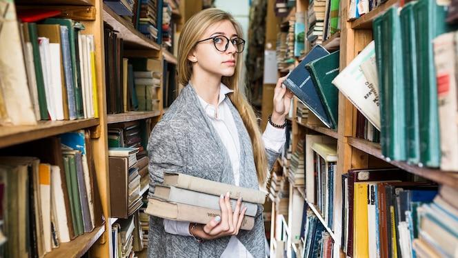 Mujer bonita recogiendo libros en la biblioteca