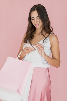 Mujer bonita con redes de compras escribiendo en el teléfono inteligente