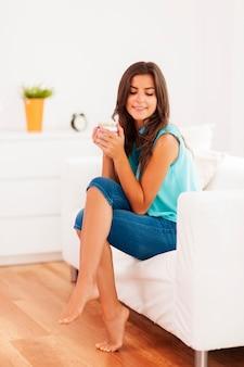Mujer bonita relajante con taza de café en casa